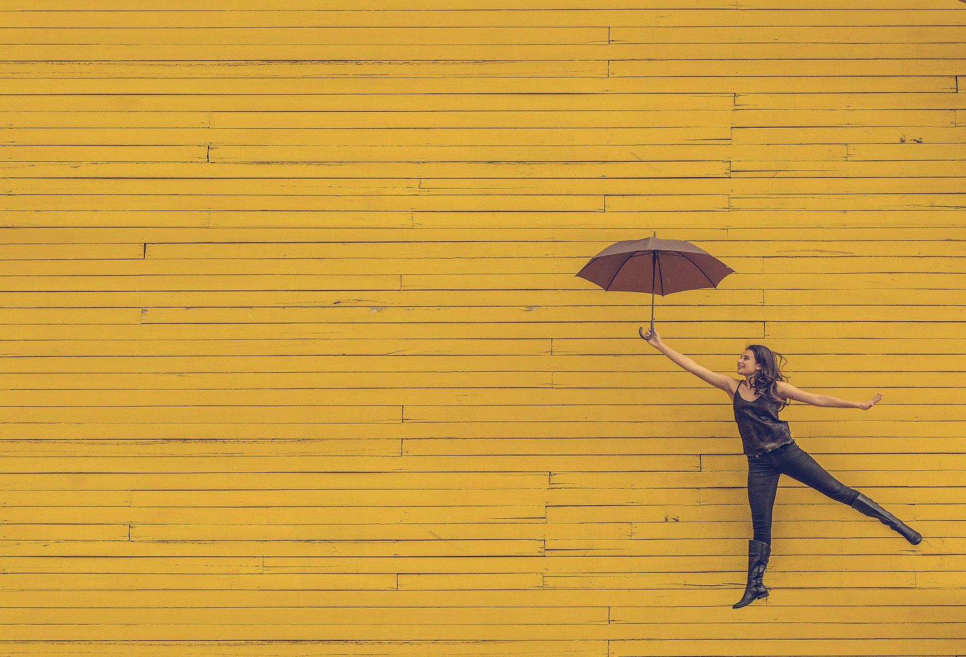 Eine Frau tanzt schwebend mit Regenschirm